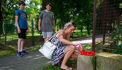 Žena zapaluje 9. srpna 2020 svíčku za oběti u pietního místa blízko domu v...