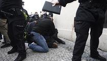 Policisté zasahují proti muži vedle shromáždění kritiků vládních opatření proti...