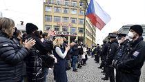 Policisté (vpravo) dohlížejí na shromáždění kritiků vládních opatření proti...