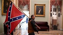 Podporovatel Donalda Trumpa uvnitř budovy Kapitolu třímající konfederační...