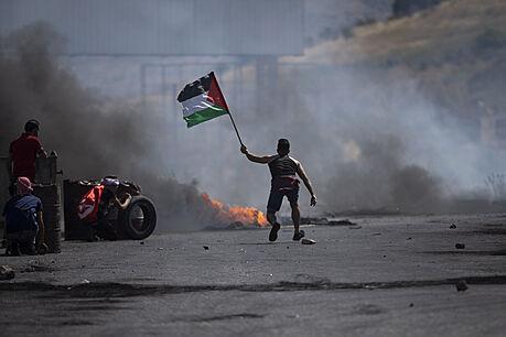 Demonstrant mává palestinskou vlajkou během střetů s izraelskımi silami na...