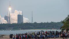 Lidé na pláži v čínské provincii Chaj-nan sledují start rakety Dlouhı pochod 5B.
