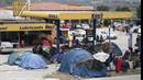 Čerpací stanice obsazená stany uprchlíků, které obírají o peníze převaděči. Je...