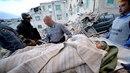 Záchranáři vynášejí jednoho z desítek lidí, které ve střední Itálii zasypalo...