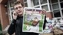 Šéfredaktor Stéphane Charbonnier drží v ruce vydání svého časopisu s...