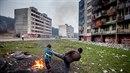 Sídliště Lunik IX je plné odpadků mezi kterými si hrají malé děti.