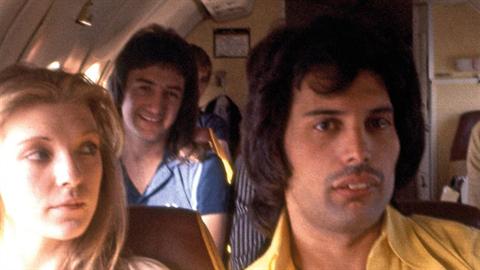 John Deacon (vzadu) a Freddie Mercury během soukromého letu.
