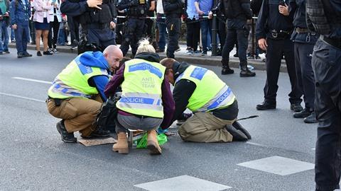 Přilepeným aktivistům museli pomoct členové anti-konfliktního týmu.