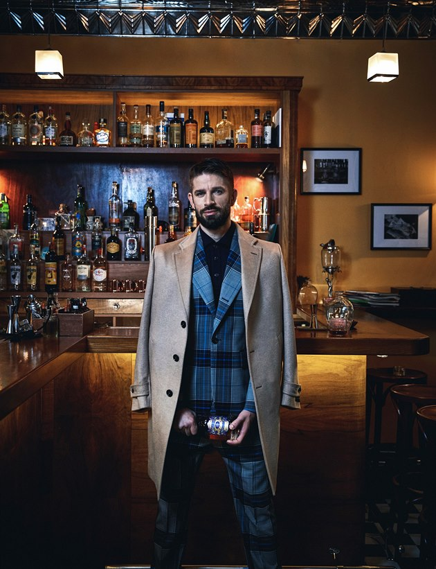 Béžový kašmírový kabát (74 820 Kč) Ermenegildo Zegna, tmavě modré úpletové polo triko ze směsi vlny, kašmíru a hedvábí (21 170 Kč) Brunello Cucinelli, vlněné kostkované sako (27 700 Kč) a kalhoty (13 100 Kč) Vivienne Westwood, The Store.