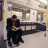 A man wears a mask as he reads on a tube in London, Monday, March 16, 2020. For...