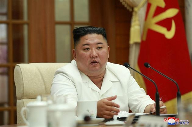 Kim Čong-un v bílém saku a s cigaretou v ruce.