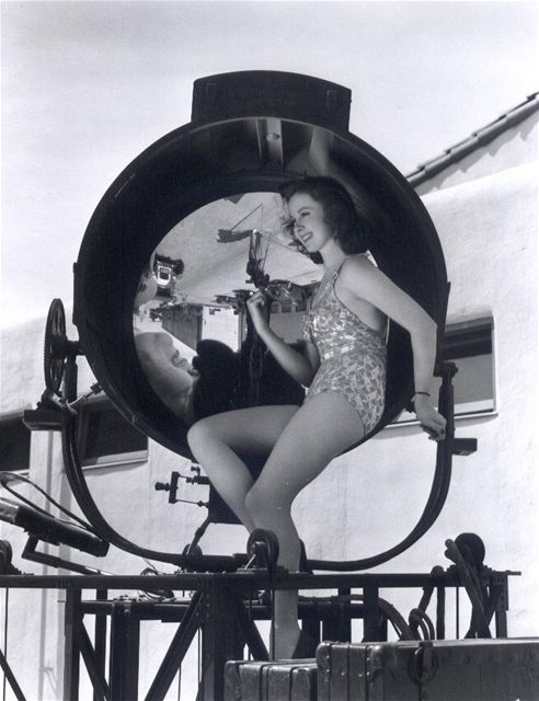Pinup girl Susan Hayward poses with a 1930s Hollywood searchlight