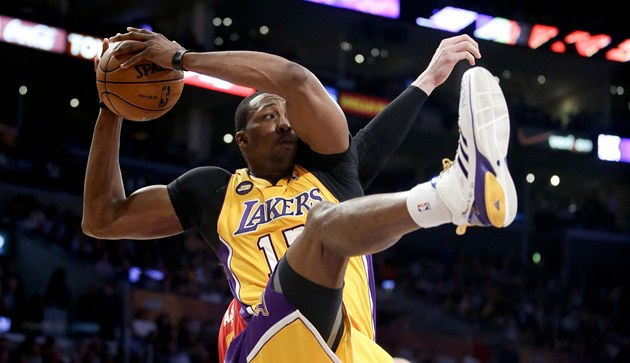 Dwight Howard z Los Angeles Lakers ve výskoku postrčený jedním z hráčů
