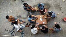 Migrant construction workers gamble with cards after a shift at a construction...