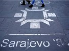 People walk past the logo of the Winter Olympics in Sarajevo, painted on the...