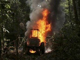 A tractor used to drag logs out of the Amazon rainforest, burns after being...