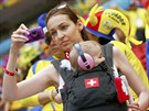 A fan of Switzerland carrying a child, takes a photo before their 2014 World...