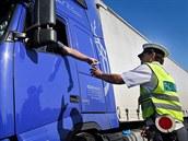 Řidič kamionu podává doklady policistovi při silniční kontrole u Býkve na...