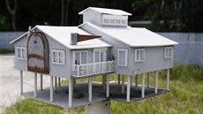 A mailbox in the shape of a house with a veranda and a parking lot is seen...