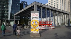People walk past a segment of the former Berlin Wall at Potsdamer Platz square...