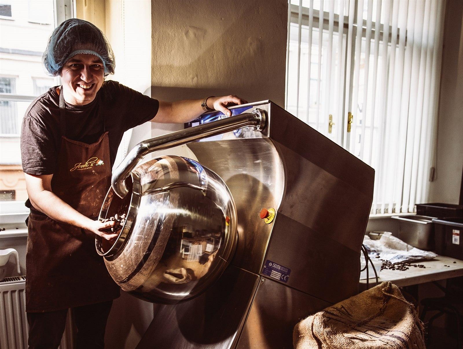 Nejnovějším přírůstkem do výrobny je moderní naleštěný nerezový dražér. Slouží k rovnoměrnému obalení kakaových bobů, kávovýh zrn či ořechů čokoládou. Jiří u této míchačky stojí celé dvě hodiny a postupně přilévá čokoládu, až vzniknou hladké kuličky.