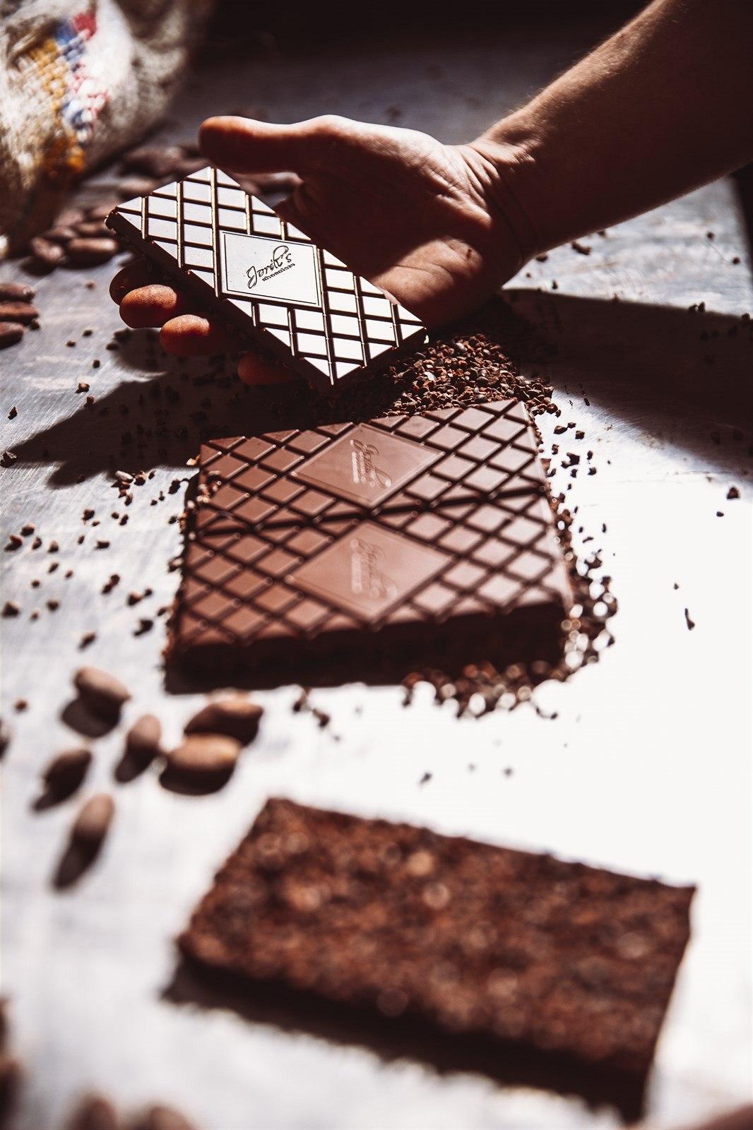 Při pohledu na dokonalý tvar jednotlivých tabulek se nechce věřit, že jsou výsledkem ruční výroby. Tmavá čokoláda se v mlýnku mele s cukrem, mléčná ještě se sušeným kravským, kozím či ovčím mlékem, do čokolády totiž smí přijít pouze suché přísady.