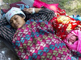 Maya Tamang, 20, sleeps next to her one-day-old daughter at a makeshift...