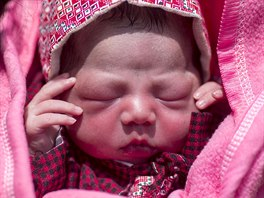 Maya Tamang's one-day-old daughter lies at a temporary makeshift outside...
