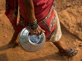 Sakhri, second wife of Sakharam Bhagat, carries an empty metal pitcher as she...