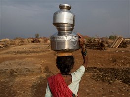 Sakhri, the second wife of Sakharam Bhagat carries a metal pitcher filled with...