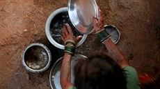Sakhri, the second wife of Sakharam Bhagat washes utensils outside their house...