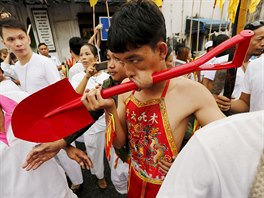 A devotee of the Chinese Bang Neow shrine with a shovel pierced through his...