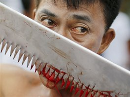 A devotee of the Chinese Bang Neow shrine cuts his tongue to make it bleed...