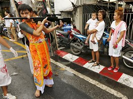 People look as a devotee of the Chinese Bang Neow shrine with a rifle pierced...