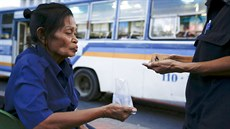 Pranom Chartyothin, a 72-year-old bus conductor, counts coins with a colleague...