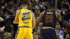 Stephen Curry (vlevo) a LeBron James sledují hru.