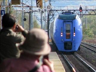Cestující si fotí příjezd expresu Super Ozora do stanice Šintoku na trati z...