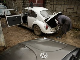 A mechanic works on the engine of a Volkswagen Beetle car in a garage in Addis...