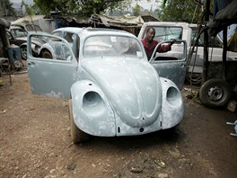 A mechanic pushes a Volkswagen Beetle car inside a garage in Addis Ababa,...