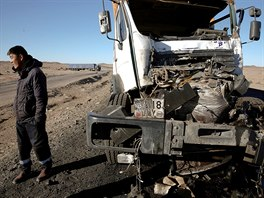 A man stands by a damaged truck after an accident en-route to China...