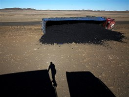 A photographer casts his shadow near a coal truck which flipped over at...