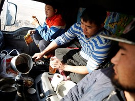 Three men eat a dinner of instant noodles and dried beef inside a truck at...