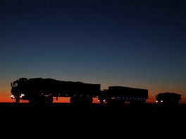 Trucks carrying coal are seen on the road as darkness descends on the route to...