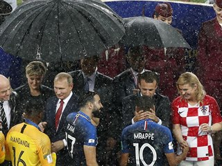 Zatímco ruský prezident Vladimir Putin se před deštěm schovává pod deštníkem,...