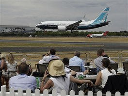 Spectators watch a Boeing 737 land after a flying display at the Farnborough...