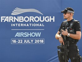 An armed police officer stands guard at Farnborough International Airshow in...