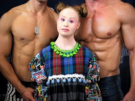 Model Madeline Stuart stands backstage between two male models at New York...