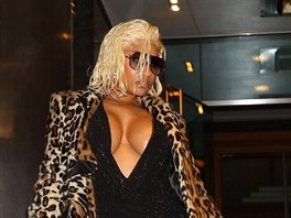Nicki Minaj lets it all hang out as she steps out in a leopard print fur and...