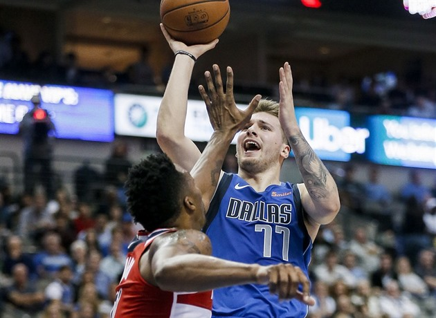 Luka Dončič (77) z Dallasu střílí přes Dwighta Howarda z Washingtonu.