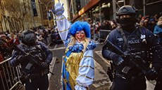 A clown performs as heavily armed police stand guard along Sixth Avenue during...